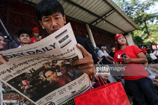 A National League for Democracy supporter sit reading a newspaper outside the party headquarters in Yangon Myanmar on Monday Nov 9 2015 Myanmar...