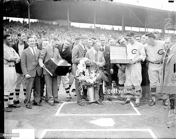 National League's Chicago Cubs baseball player Koehler holding an open box or case standing with a group of unidentified men at home plate during an...