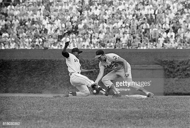"""National League's Willie Mays hustles back to 1st to beat """"pickoff attempt"""" by American League pitcher Ray Herbert here, as 1st baseman Jim Gentile..."""