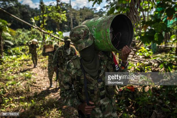 A National Liberation Army guerrilla carries explosives with homemade mortars known as a pipetas to test in a remote village in Choco Department...