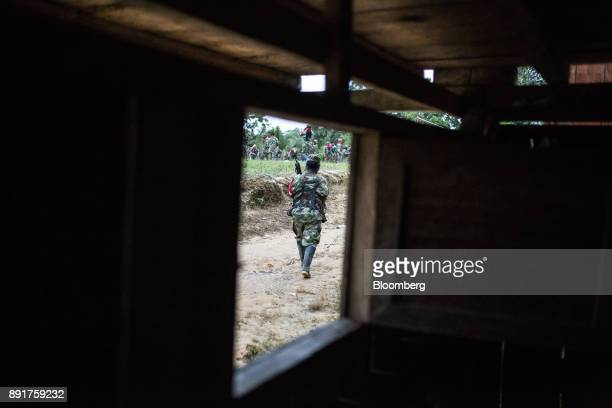A National Liberation Army guerrilla is seen from the window of a home walking towards morning training exercises in a remote village in Choco...