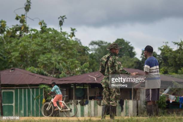 A National Liberation Army guerrilla left shakes hands with a local resident in a remote village in Choco Department Colombia on Friday Nov 17 2017...