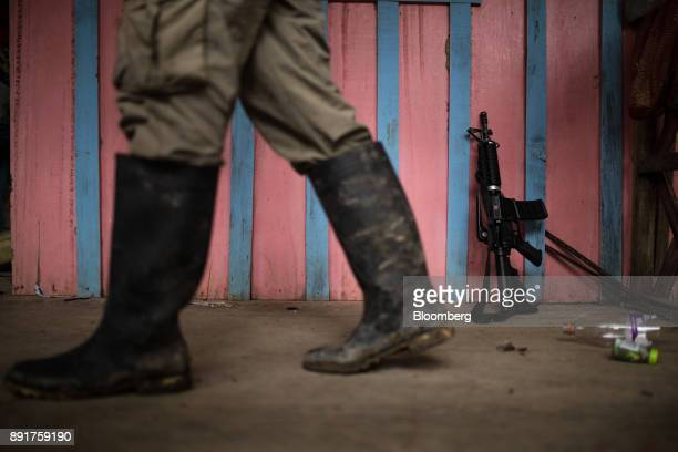A National Liberation Army guerrilla walks past a weapon leaning on a wall in a remote village in Choco Department Colombia on Friday Nov 17 2017 The...