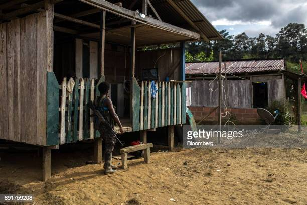 A National Liberation Army guerrilla watches television powered with a gasoline generator from outside a home in a remote village in Choco Department...