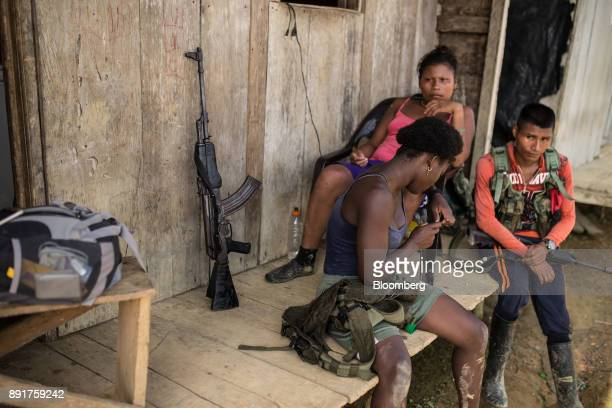 National Liberation Army guerrillas sit outside a home in a remote village in Choco Department Colombia on Saturday Nov 18 2017 The Cold War ended a...