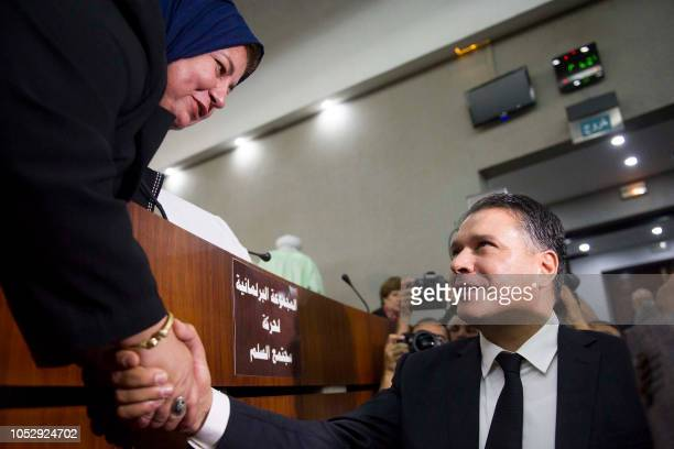 National Liberation Front's member and newly elected president of parliament Mouad Bouchareb shakes hands with a woman at the Algerian National...