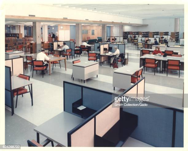 National Library of Medicine's main reading room people are studying at cubicles with shelves full of books on one side Bethesda Maryland 1960