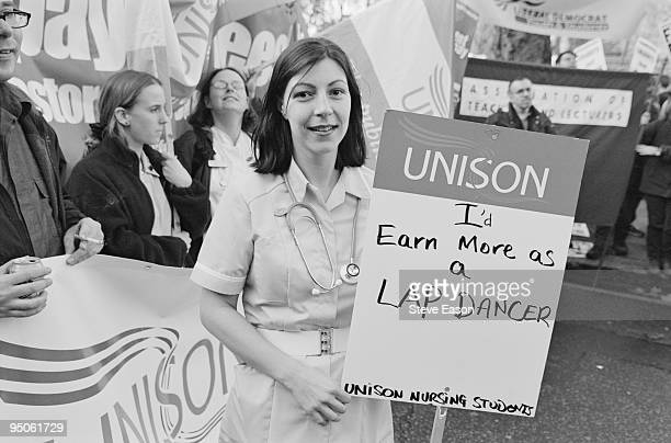 A National March for Education by the NUS in London 25th November 1999 A student nurse is carrying a UNISON placard with the words 'I'd earn more as...