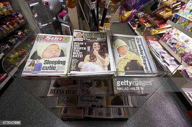 National newspapers display pictures of the new daughter of Britain's Prince William and wife Kate on their front covers in a newsagents in London on...