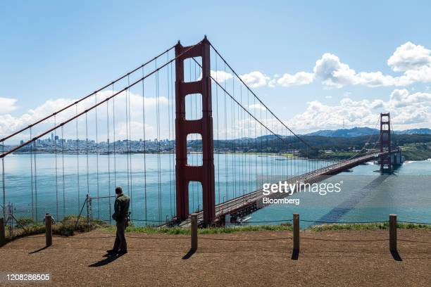 National Park Ranger looks out over the Golden Gate Bridge in Sausalito, California, U.S., on Thursday, March 26, 2020. Governor Newsom on March 19...