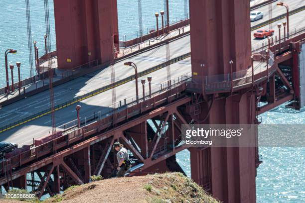 National Park Ranger walks down a trail at the Golden Gate Bridge in Sausalito, California, U.S., on Thursday, March 26, 2020. Governor Newsom on...