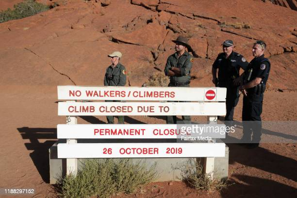 National park rangers erect a sign marking the closure of the walking track to the summit of Uluru in the Northern Territory, October 25, 2019. The...