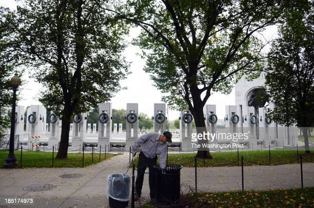National Park Service employee John Wehrli empties trash cans along the WWII memorial which reopened shortly after the end of the government shutdown