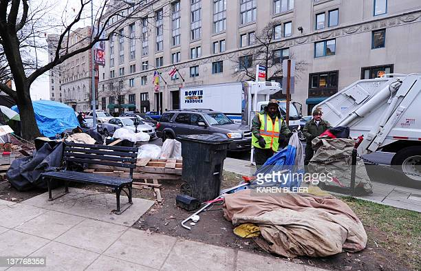 National Park Service employees Garey Bickham and George Stinnie pick up trash at the Occupy DC encampment in McPherson Square in Washington DC...
