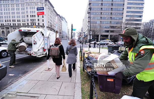 National Park Service employees Garey Bickham and George Stinnie throw trash into the back of a garbage truck at the Occupy DC encampment in...