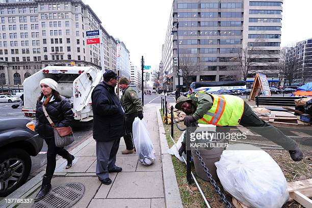 National Park Service employees Garey Bickham and George Stinnie throw trash into the back of a garbage truck as a passerby looks on at the Occupy DC...