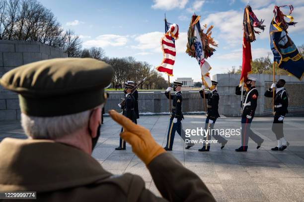 National Park Service Living History volunteer Patrick McCourt salutes as a military honor guard departs the World War II Memorial after a wreath...