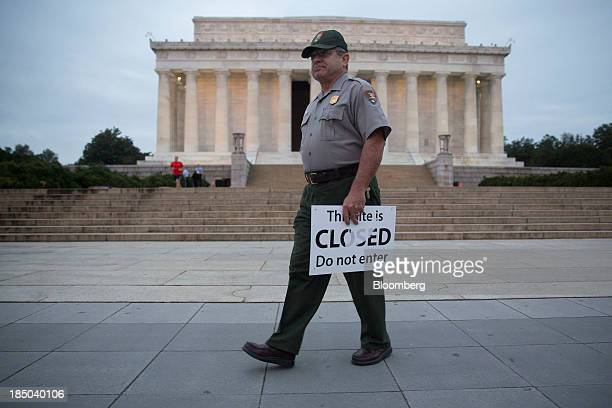 National Park Service park ranger Richard Trott holds a closed sign he removed at the Lincoln Memorial in Washington DC US on Thursday Oct 17 2013...