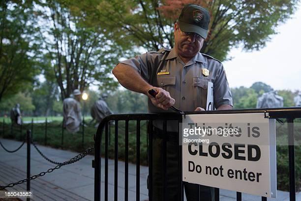 National Park Service park ranger Richard Trott removes a closed sign at the Korean War Veterans Memorial in Washington DC US on Thursday Oct 17 2013...