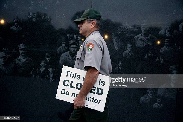 National Park Service park ranger Richard Trott walks through the Korean War Veterans Memorial with a closed sign he removed in Washington DC US on...