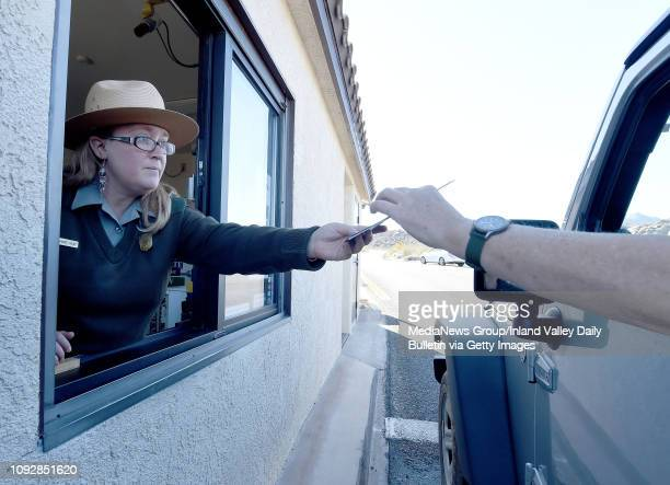 National Park Service Ranger Anna Marie Gilay who has not worked in over 2 weeks hands out a Joshua Tree National Park map to a visitor Thursday...