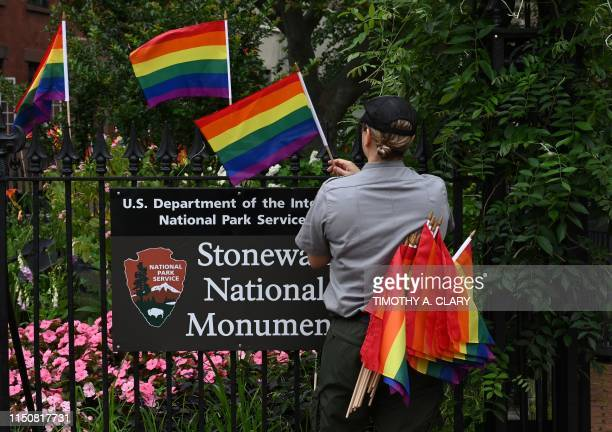 National Park Service ranger places rainbow flags on the fence at the Stonewall National Monument in the West Village neighborhood of Greenwich...