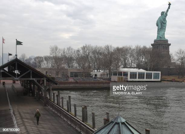 A National Park Service Ranger walks out to greet the first visitors to arrive Monday morning at the Statue of Liberty January 22 2018 in New York...