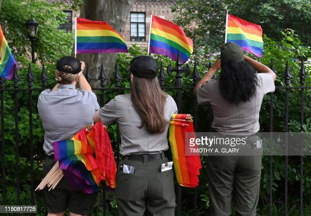 National Park Service rangers place rainbow flags on the fence at the Stonewall National Monument in the West Village neighborhood of Greenwich...