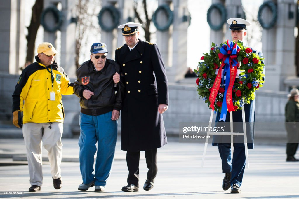 A National Park Service volunteer escorts Retired Air Force Staff Sgt. Bill Hare, 91, as he places a wreath during a ceremony held by the Friends of the National World War II Memorial and the National Park Service, to commemorate Pearl Harbor Remembrance Day on December 7, 2017 in Washington, DC. World War II veterans and Pearl Harbor survivors placed wreaths at the Freedom Wall to commemorate the more than 400,000 Americans who lost their lives during World War II, including the more than 2,400 who lost their lives on December 7, 1941.