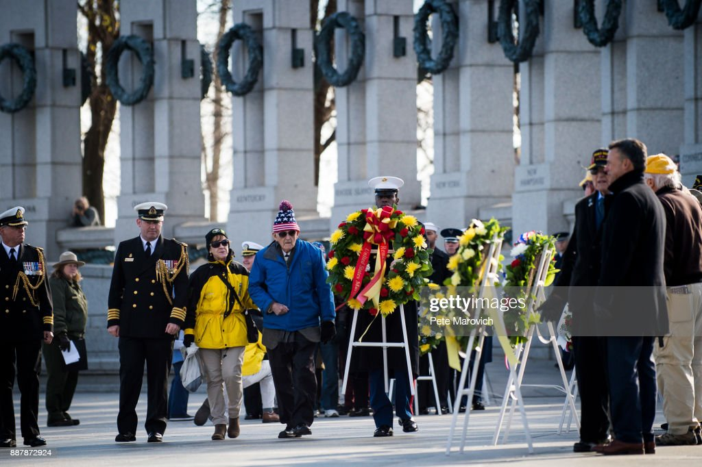 A National Park Service volunteer escorts Retired Army Col. Edward Padelford, 91, as he places a wreath during a ceremony held by the Friends of the National World War II Memorial and the National Park Service, to commemorate Pearl Harbor Remembrance Day on December 7, 2017 in Washington, DC. World War II veterans and Pearl Harbor survivors placed wreaths at the Freedom Wall to commemorate the more than 400,000 Americans who lost their lives during World War II, including the more than 2,400 who lost their lives on December 7, 1941.