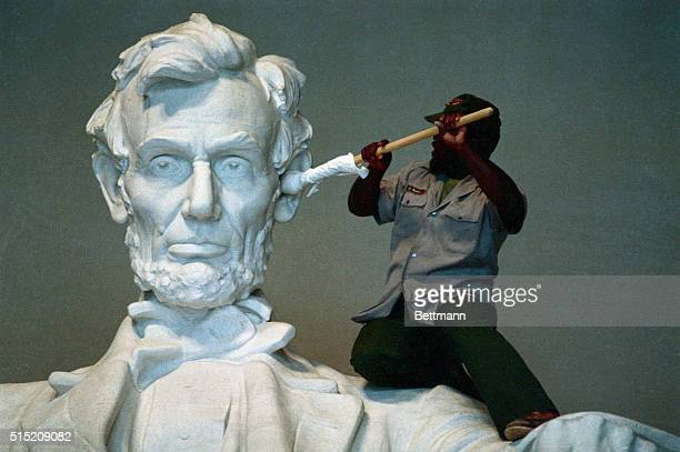 National Parks Service workman James Hudson uses a cloth wrapped pole to clean the ear of the statue at the Lincoln Memorial | Detail of 'Lincoln' by...