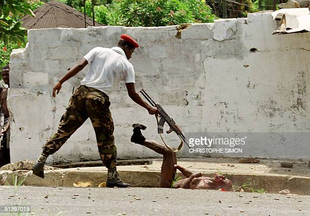 National Patriotic Front of Liberia fighter gives the coup de grace to an enemy Krahn fighter 08 May 1996 after a patrol capturing and stripping him...