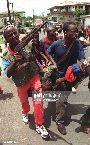 National Patriotic Front of Liberia fighters carry a wounded comrade after a fight against ULIMOMandingo fighters in a street of Monrovia 19 April...