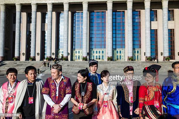 National People's Congress staff wearing ethnic minorities traditional dress pose for a picture during the third plenary session of the National...