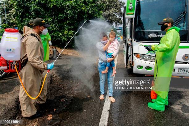 TOPSHOT National Police members disinfect Venezuelan citizens returning to the country from Colombia as a preventive measure against the spread of...