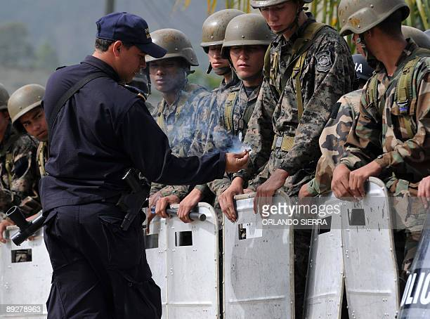 A National Police officer jokes with soldiers as they all block the road to Alauca 10 km north of Las Manos near the border with Nicaragua on July 27...