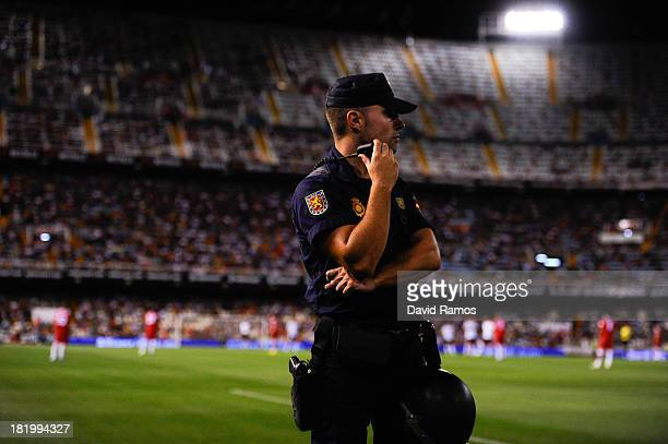 A national police officer stands guard on the pitch prior to the La Liga match between Valencia CF and Sevilla FC at Estadio Mestalla on September 22...