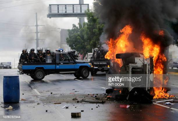 National Police officers in riot gear drive next to an overturned burning police vehicle after an antigovernment protest in Managua on September 2...