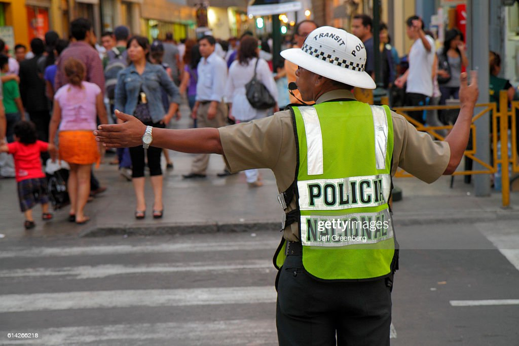 National police traffic cop helping people to cross the road of the historic district of Jiron de la Union. : News Photo