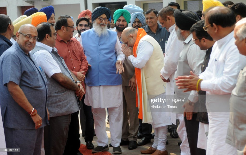National President Amit Shah greets former Chief Minister Parkash Singh Badal as SAD President Sukhbir Singh Badal and other leaders look on at MLA...