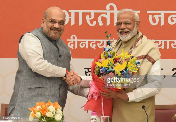 National president Amit Shah presents a bouquet to Prime minister Narendra Modi during a meeting of the Union Council of Ministers to thank them to...
