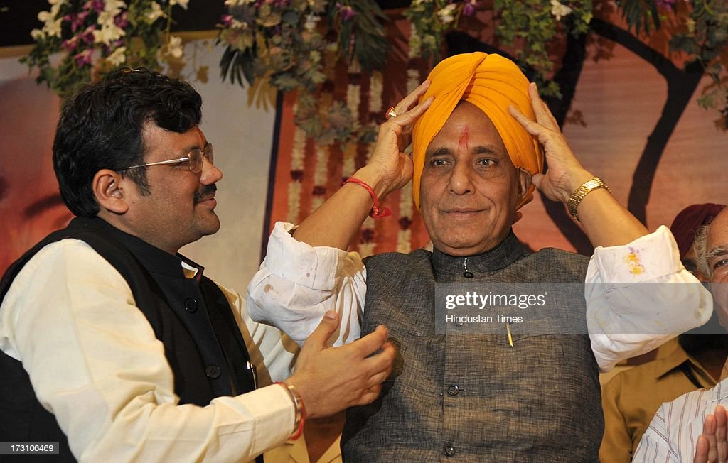 BJP National President Rajnath Singh adjusting his turban after being presented by the BJP Punjab President Kamal Sharma during the BJP State executive meeting on July 7, 2013 in Amritsar, India. BJP leaders discuss all the matters relating the preparedness for the next parliamentary polls and its ties with the alliance partner in the state Shiromani Akali Dal (Badal).