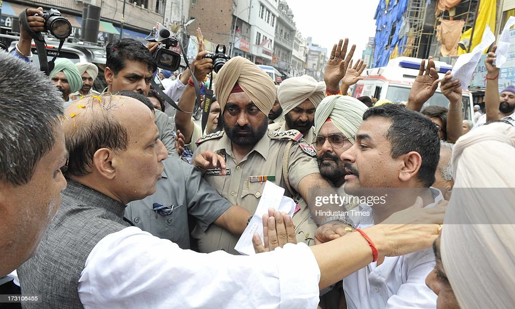 BJP National President Rajnath Singh listening the grievances of the victim shopkeepers, who going to be uprooted after demolishing their shops for clearing the way for long proposed 40feet wide road to Golden Temple, outside the Jallianwala Bagh on July 7, 2013 in Amritsar, India. BJP leaders discuss all the matters relating the preparedness for the next parliamentary polls and its ties with the alliance partner in the state Shiromani Akali Dal (Badal).