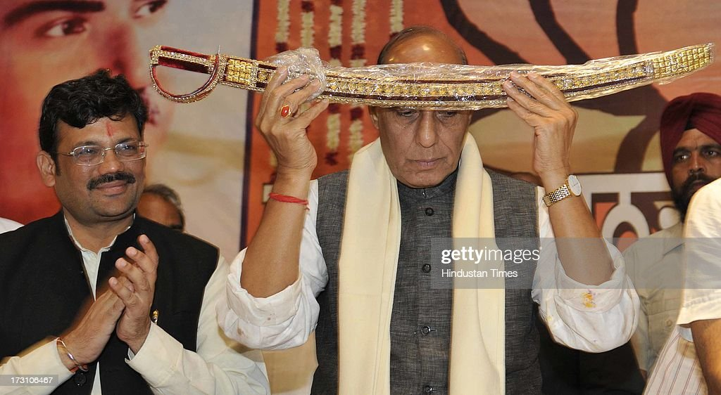 BJP National President Rajnath Singh paying regard to a sword after being presented to him by state BJP during the BJP State executive meeting on July 7, 2013 in Amritsar, India. BJP leaders discuss all the matters relating the preparedness for the next parliamentary polls and its ties with the alliance partner in the state Shiromani Akali Dal (Badal).