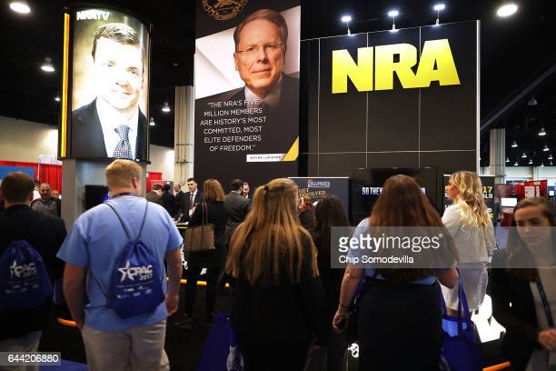 National Rifle Association CEO Wayne LaPierre's image floats above the NRA booth in the Exhibitor Hub during the first day of the Conservative...