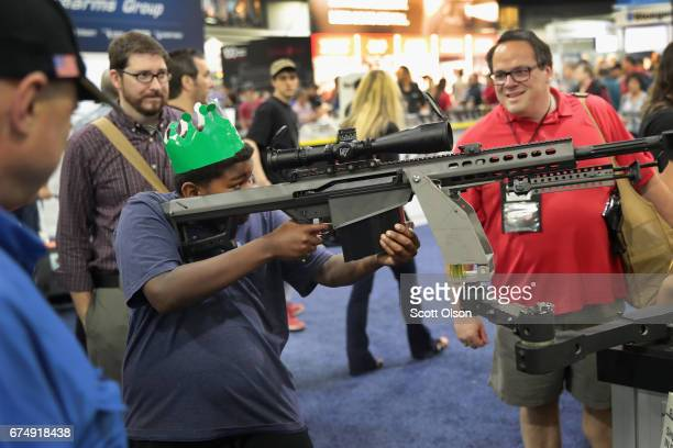National Rifle Association members look over guns in the Barrett display at the 146th NRA Annual Meetings Exhibits on April 29 2017 in Atlanta...