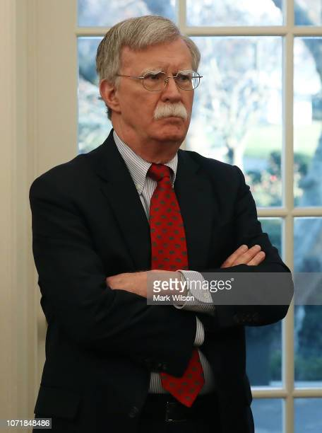 """National Security Adviser John Bolton attends a meeting in the Oval Office where U.S. President Donald Trump signed H.R. 390, the """"Iraq and Syria..."""