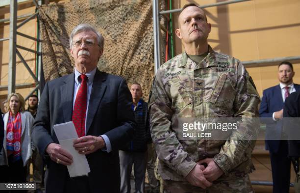 US National Security Adviser John Bolton listens as US President Donald Trump speaks to members of the US military during an unannounced trip to Al...