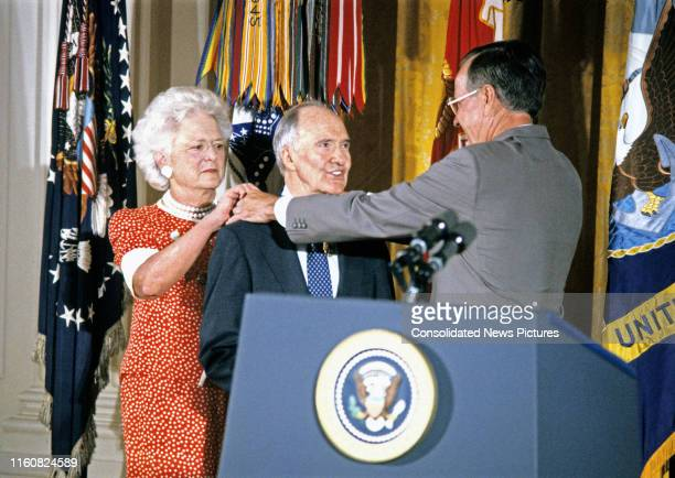 National Security Advisor Brent Scowcroft smiles as American First Lady Barbara Bush and US President George HW Bush fasten the Presidential Medal of...