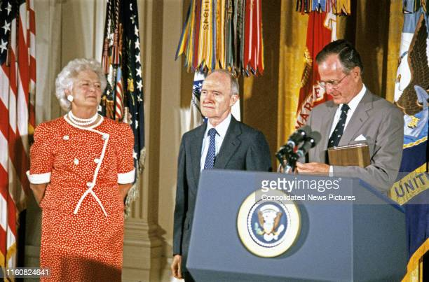 National Security Advisor Brent Scowcroft stands between First Lady Barbara Bush and US President George HW Bush during his Presidential Medal of...